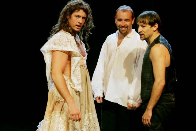 Three men stand performing a Shakespeare play, one dressed as a woman.