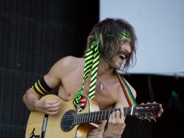 Eugene Hütz strums an acoustic guitar while topless with a necktie around his head,