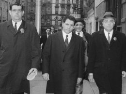Three men in suits walk towards the camera