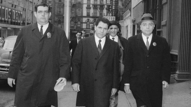 Three men in suits walk towards the camera