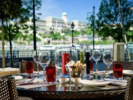A table ready for people to be seated, outside on a sunny day, with the Hungarian National Gallery in the background. Courtesy of the peppers! website