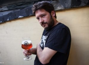 Dániel Bart holds a glass of beer. Courtesy of index.hu